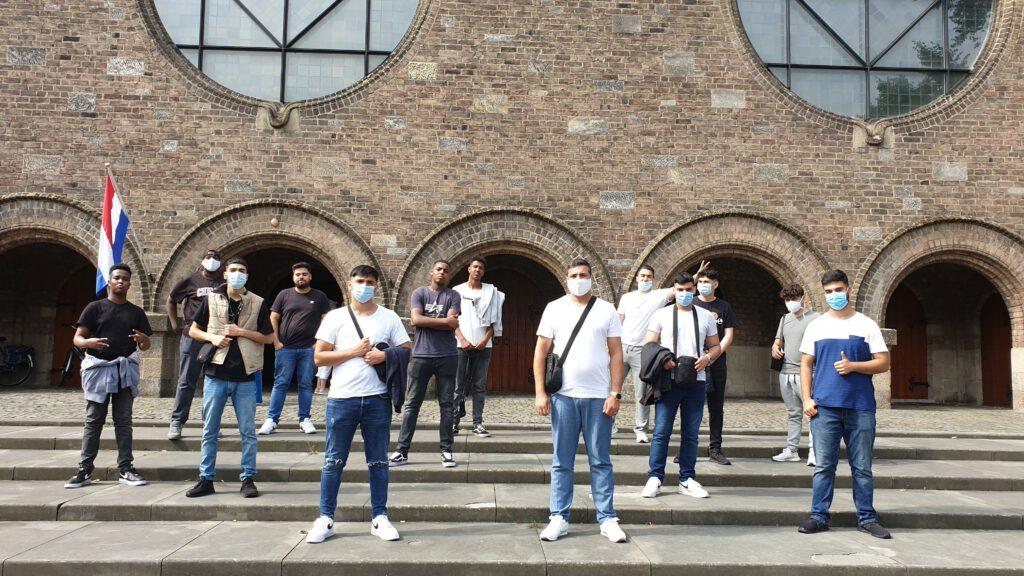 Die Jungengruppe des Jugendsalons des Begegnungszentrums Kinderhaus vor der Kirche am Alten Markt in Enschede.