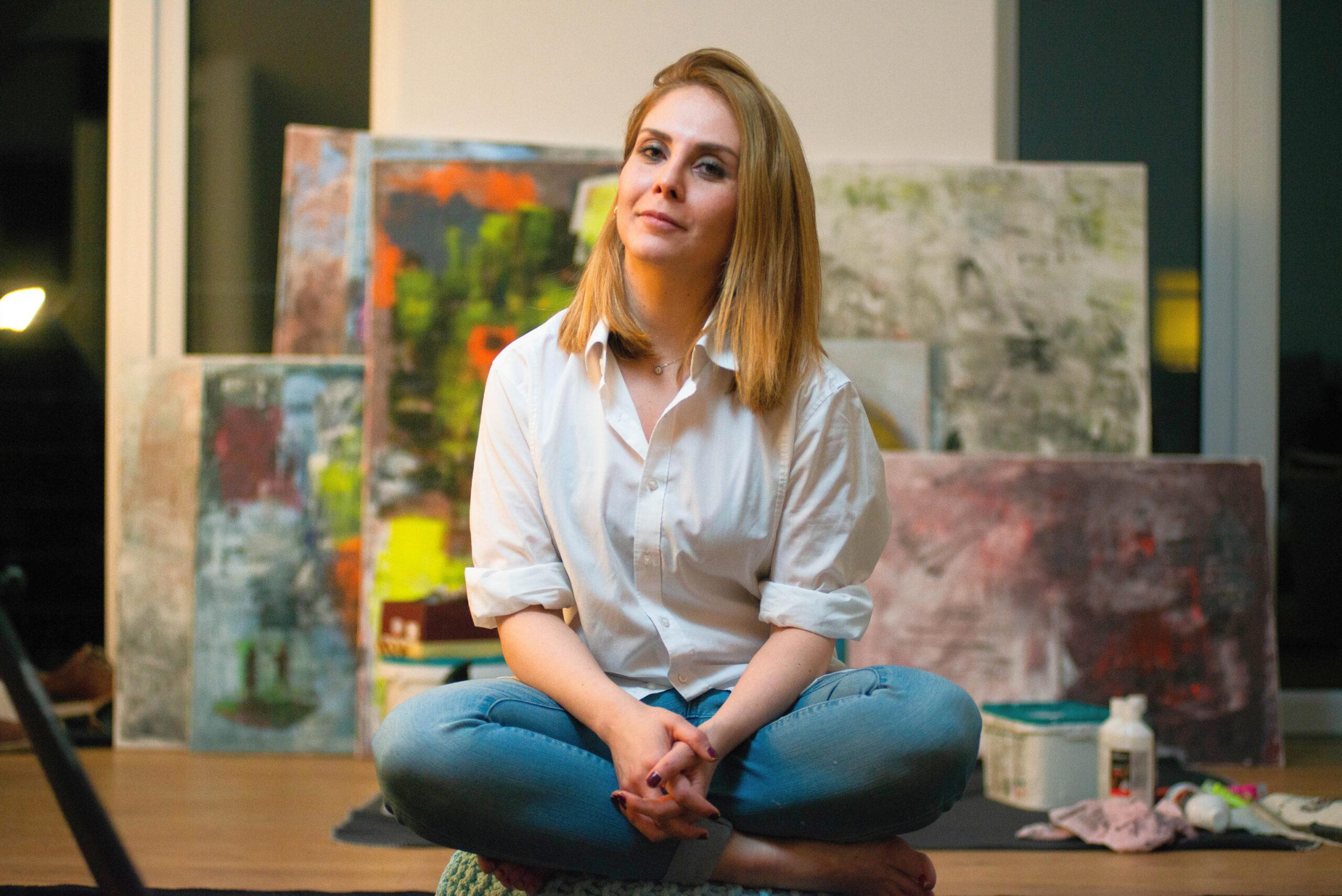Die Künstlerin Khadija Batti im Schneidersitz vor ihren Gemälden.