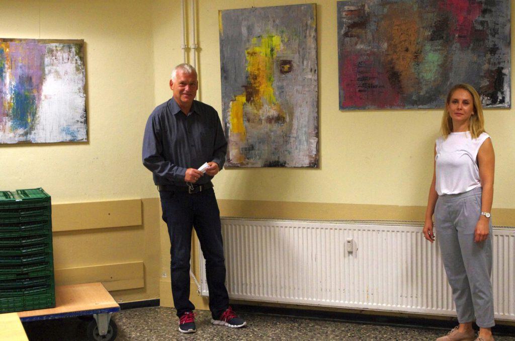 Thomas Kollmann, Geschäftsführer des Begegnungszentrums Kinderhaus, und die Malerin Khadija Batti vor zwei Gemälden der Künstlerin.
