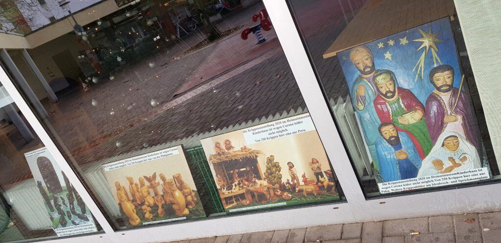 Vier Weihnachtskrippenfotos im Fenster des Begegnungszentrums Kinderhaus